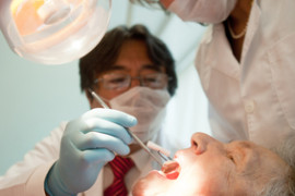 Dentist working on an elderly patient with cognitive decline.